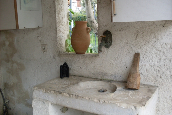A very old stone block with a shallow sink cutout used as a hand washing sink in a in Tuscan farmhouse.