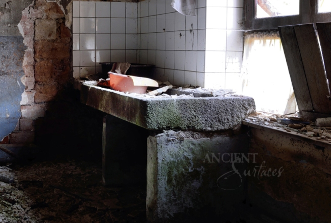A massive antique thick slab sink seen with three supportive limestone legs.